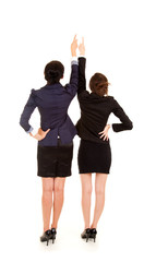 two young business women standing back and pointing up