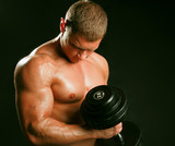 Unknown muscular man working out with dumbbells