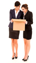 two happy young business women with carton box