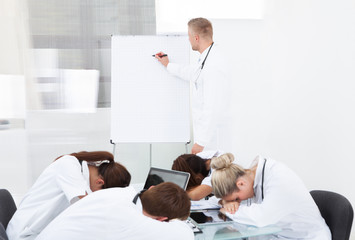 Doctor Giving Presentation To Colleagues Sleeping At Desk