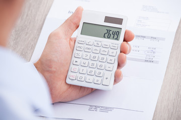 Businessman's Hands Calculating Invoice At Desk
