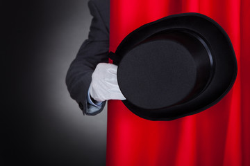Magician Holding Hat Behind Stage Curtain