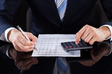 Businessman Calculating Financial Expenses At Desk
