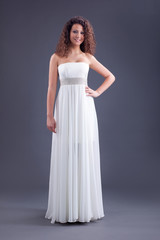 Young beautiful curly female model in white dress