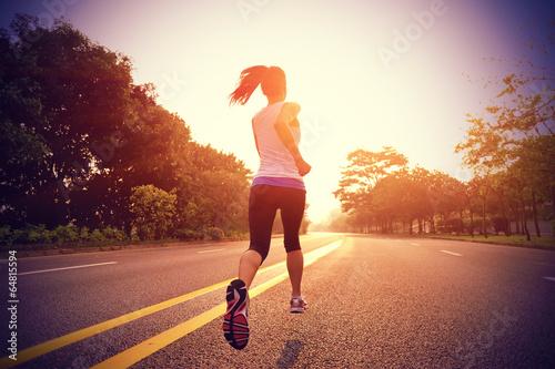 Runner athlete running on sunrise road - 64815594