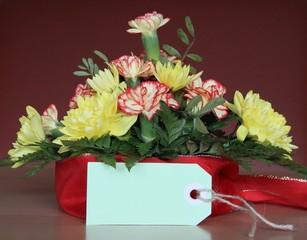 Gesteck frischer Blumen mit Schleife und Textfreiraum