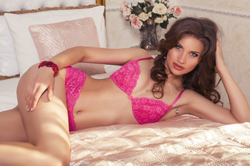 sexy woman in pink lingerie lying on bed at bedroom