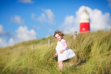 Cute toddler girl next to red lightshouse on a beach