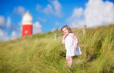Adorable toddler girl next  red lightshouse on a beach