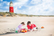 Brother and sister playing on the shore next to lighthouse