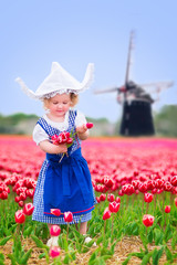 Pretty girl in Dutch costume in tulips field next windmill