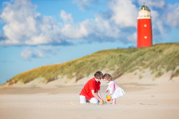 Happy brother and his sister playing on beach next to lighthouse