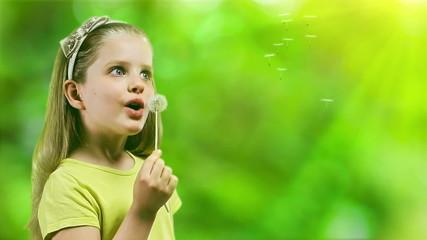 Child blowing on dandelion