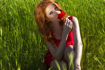 beautiful woman with red hair relaxing on grass field