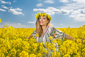 Young girl wearing Romanian traditional blouse posing in canola