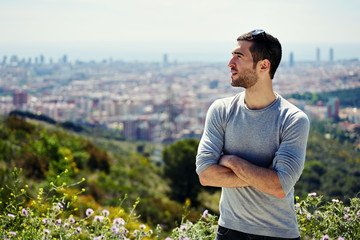 man looking aside on the background of a big city panorama