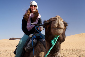 Young woman in desert riding a camel