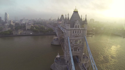 Camera flying above London Bridge over Thames river. At sunset.
