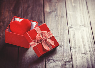 Red gift box with toy heart inside on wooden table.