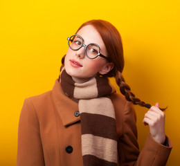 Redhead girl scarf and coat on yellow background.