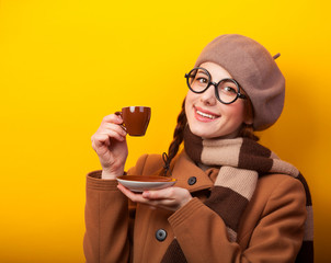 Redhead girl with coffee on yellow background