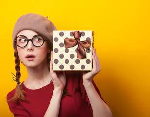 Redhead girl with suitcase on yellow background.