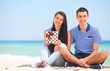 Young couple with gift on the beach in summer day.