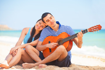 Young couple with guitar on the beach in summer day.