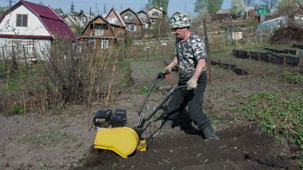 The gardener processes the earth a motor-cultivator