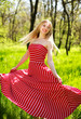 Adorable summer young woman in long red dress, carefree dancing