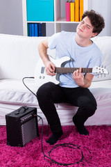 Boy playing electric guitar in his room