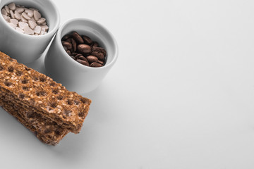 Set of saucers full of coffee beans and candy with crispbread