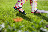 Woman wearing spiked lawn revitalizing aerating shoes poster