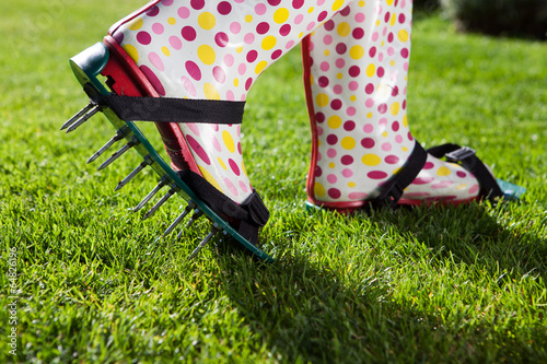 Woman wearing spiked lawn revitalizing aerating shoes - 64826196