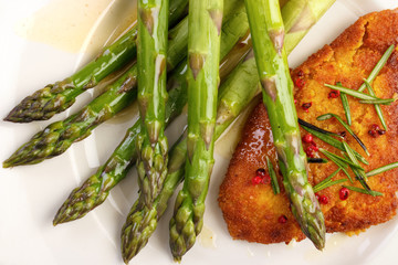Crumbed fish fillet with cooked asparagus on dish