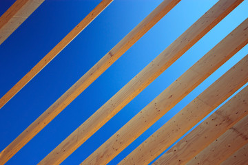 Roof rafter timbers against blue sky