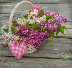 White basket with a branch of lilac and heart