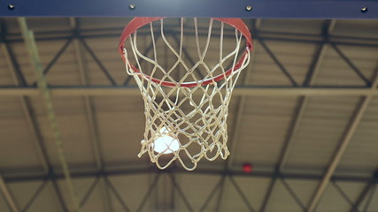 Close shot of basketball scoring through the net