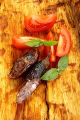 sausage, tomatoes and basil on an orange background bark