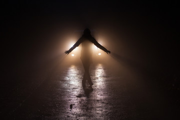 In the forest at night. Aperson stands on the road in front of t