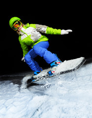 Portrait of girl jumping on snowboard at night