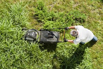 Мужчина ухаживает за газоном