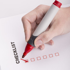 Checklist on white with marker and woman hand