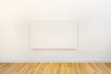 single blank canvas hanging on a white gallery or studio wall