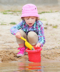 Little girl playing with bucket and spade on the beach.