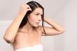 canvas print picture - Junge Frau kämmt vorsichtig Läuse aus ihrem Haar