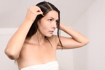 Junge Frau kämmt vorsichtig Läuse aus ihrem Haar