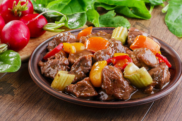 goulash meat with vegetables on the plate
