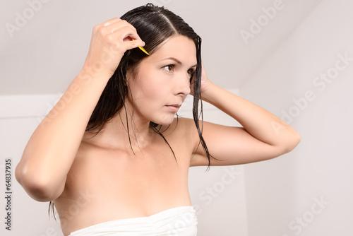 canvas print picture Junge Frau kämmt vorsichtig Läuse aus ihrem Haar