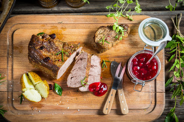 Venison and baked potato served with cranberry sauce